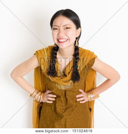 Portrait of beautiful mixed race Indian Chinese female in traditional Punjabi dress smiling, standing on plain white background.