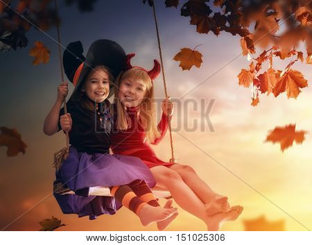 Two happy sisters on Halloween. Funny kids in carnival costumes outdoors. Cheerful children on swings on sunset background.