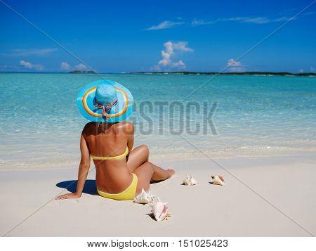 Woman in bikini sunbathing on the beach in Exuma, Bahamas.