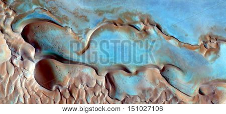 blue puzzle on the dunes of the African desert,abstract photography from the air,mirage in the desert of Africa,soft textures with sinuous forms,natural design,abstract surrealism, abstract naturalism