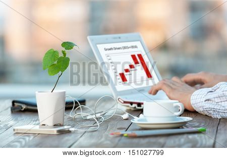 Workplace at Outdoor Patio and Hands of Person smart casual clothing typing on Laptop electronic Gadgets color Pencils green Flower with Focus on plant leaves