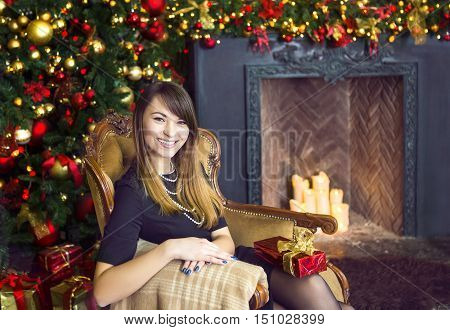 Portrait of happy young woman sittting in armchair near the Christmas tree