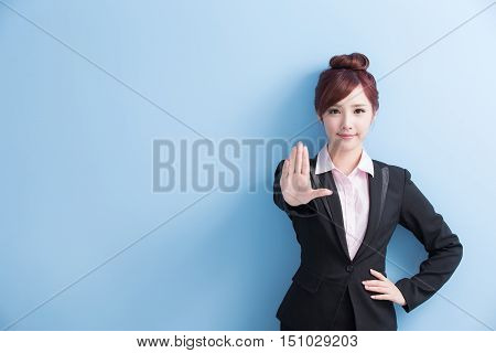 business woman do a stop gesture with isolated on blue background asian