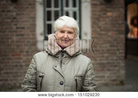 Elderly woman with gray hairs wearing winter clothes