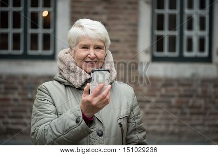 Elderly woman wearing winter clothes uses smartphone makes selfies