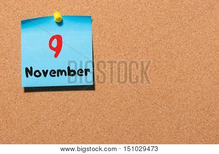 November 9th. Day 9 of month, color sticker calendar on notice board. Autumn time. Empty space for text. poster