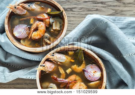 Two bowls of thai tom yum soup on the wooden table