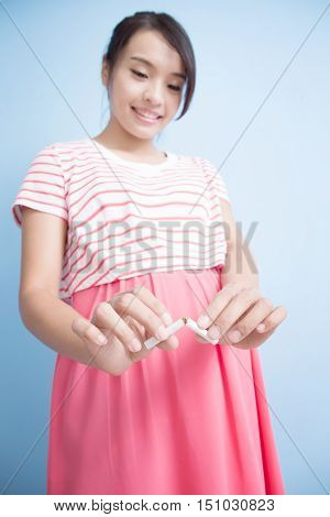 Quit smoking pregnant woman hands breaking the cigarette close upisolated on blue background