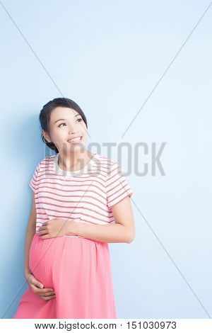 pregnant woman look somewhere and smile isolated on bluebackground asian