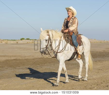 cowgirl on camargue horse on the beach