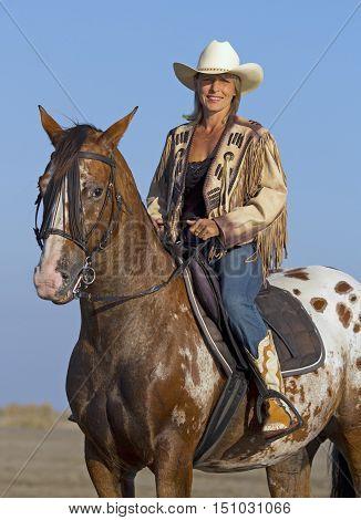 cowgirl on appaloosa horse on the beach