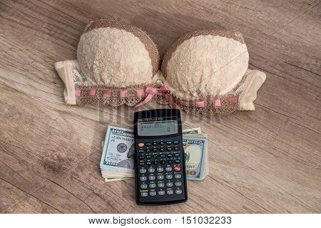 beige bra and calculator with money on desk
