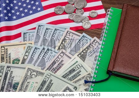 us dollar banknote with coins and flag notepad pen on table