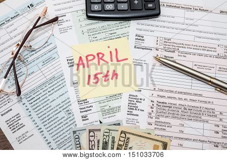 1040 tax form with sticky note of april 15 us dollar and calculator
