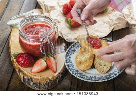 Smearing Strawberry Jam On A Toast For Breakfast