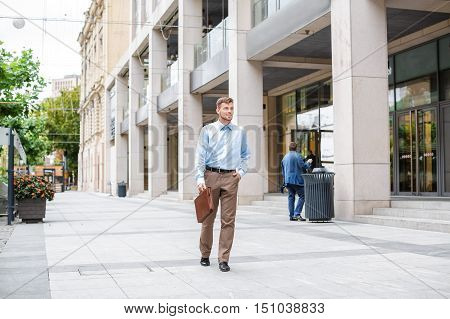 handsome Caucasian businessman walks with briefcase on the background of the city.