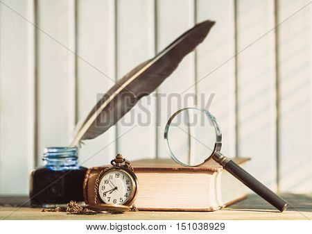 Pocket watch, quill pen, inkwell, book, magnifying glass on the table in front of wooden background