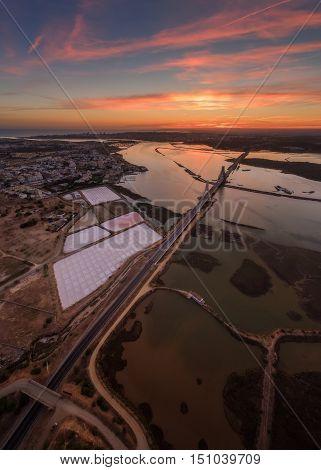 Vertical panorama the river Arade bridge. Red sunset. Portimao Portugal.