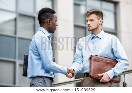 African American businessman and a Caucasian businessman shaking hands on the background buildings in the city, view from below