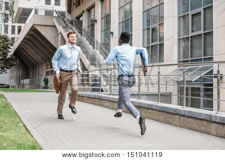 African American businessman and Caucasian businessman running to meet each other on  background of the city. clash of interests