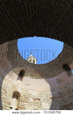 SPLIT, CROATIA - SEPTEMBER 11, 2016: There is a view of the ruined dome of the vestibule of Diocletian's Palace which is visible through the bell tower of the Cathedral of St. Domnius.