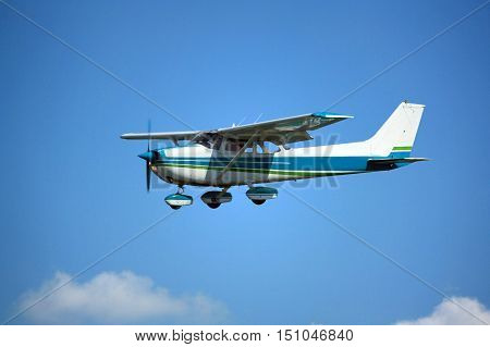 Light general aviation plane on final over green trees