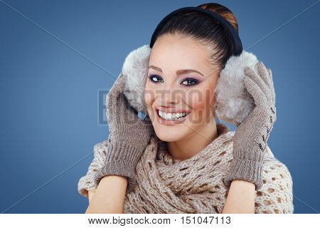 Winter fashion woman with ear muff in studio on blue background