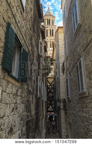 SPLIT, CROATIA - SEPTEMBER 11, 2016: This is one of the medieval streets that have arisen on the territory of the Palace of Diocletian through which you can see the bell tower of the Cathedral.