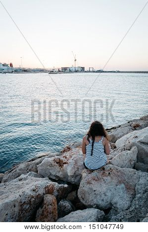 Girl sitting on the seawall rocks looking at sunset. Rear view
