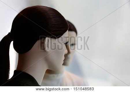 Two fashion female mannequins in brown wigs with long tail display casual clothes in shop on grey background