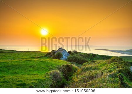 Irish cottage house near the ocean at sunset