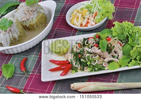 Spicy and sour mixed herb salad with pork and chicken  with side dish as mini vegetable salad and streamed gourd  wrap vermicelli and pork in soup. Selective focus.
