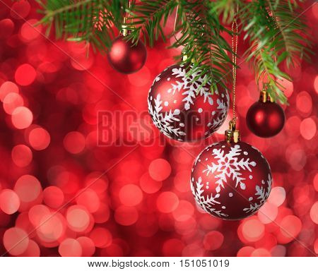 Christmas Baubles on red background with sparkles .