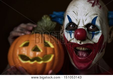 closeup of a scary evil clown holding a carved pumpkin next to his head