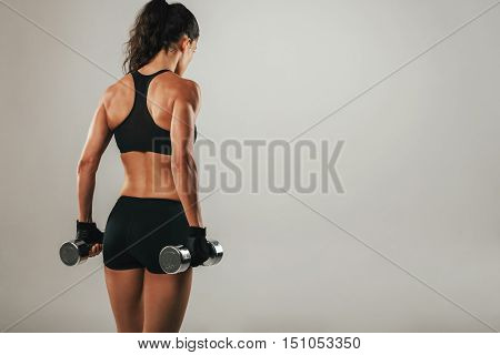 Back Of Athletic Woman Holding Weights