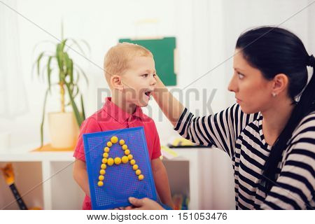 Little boy during lesson with his speech therapist. Learning through fun and play