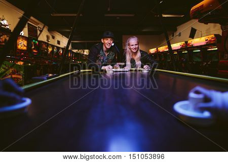 Young friends playing air hockey at amusement park. Man and woman playing a game of air hockey in the game room.