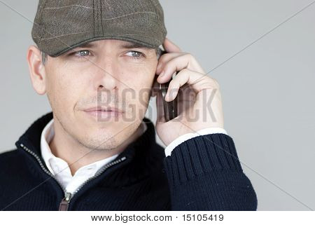 Confident Man In Newsboy Hat Talks On His Cell Phone