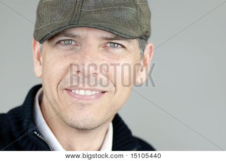 Smiling Man In Newsboy Hat Looks To Camera