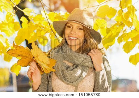 Modern beautiful young woman in park in autumn holding leaves. Portrait of cute happy teenage girl outdoors in fall. Vibrant colors, mild retouch, natural light.