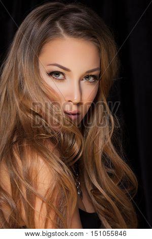 Sexy blond woman posing on dark background