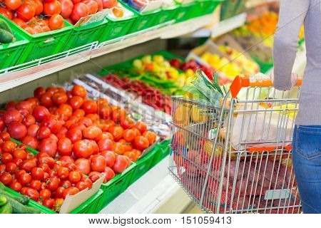 Closeup of a Woman Pushing a Shopping Cart Full of Groceries in a Supermarket
