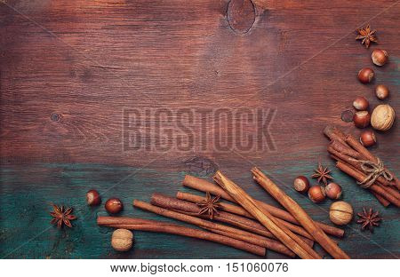Winter spices and ingredients for cooking the Christmas meal. Cinnamon sticks hazelnuts walnuts nutmeg cloves anise stars on an old wooden background (top view)
