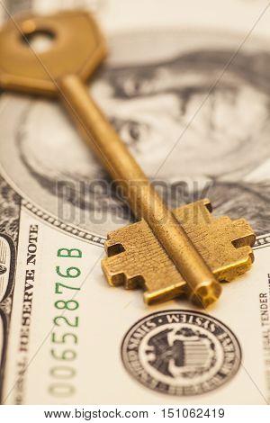 gold key on hundred dollar US bill