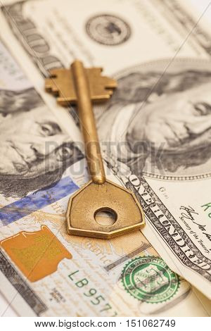 Closeup of key on hundred dollar bills