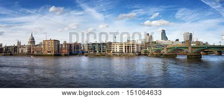 A panorama of the City of London, as viewed from the South Bank of the river Thames, with Saint Pauls Cathedral to the left and the City financial district and Southwark bridge to the right.