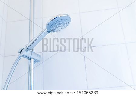 bathroom hand shower with water stream on the white tiles background