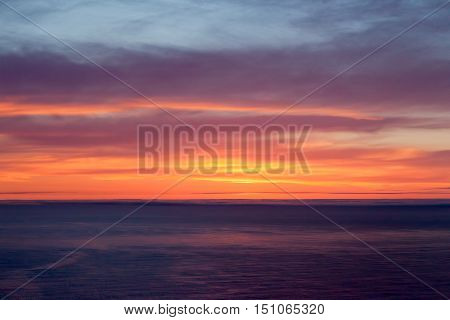 A colorful Atlantic ocean sunset with clouds.