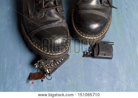 Peices of broken phone under a foot wearing black boots studio closeup