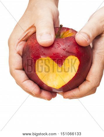 Hand with apple, which cut a heart on white
